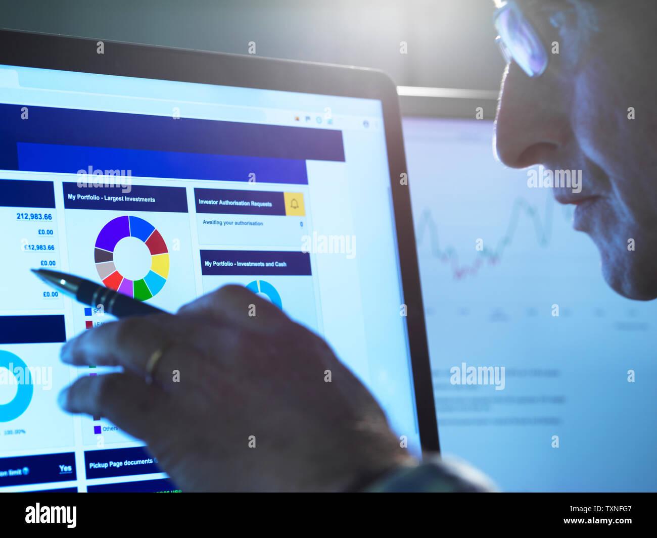 Finanzdienstleistungen, Lager der Analyst untersucht das Aktienkurs Daten eines Unternehmens auf dem Computer Stockbild