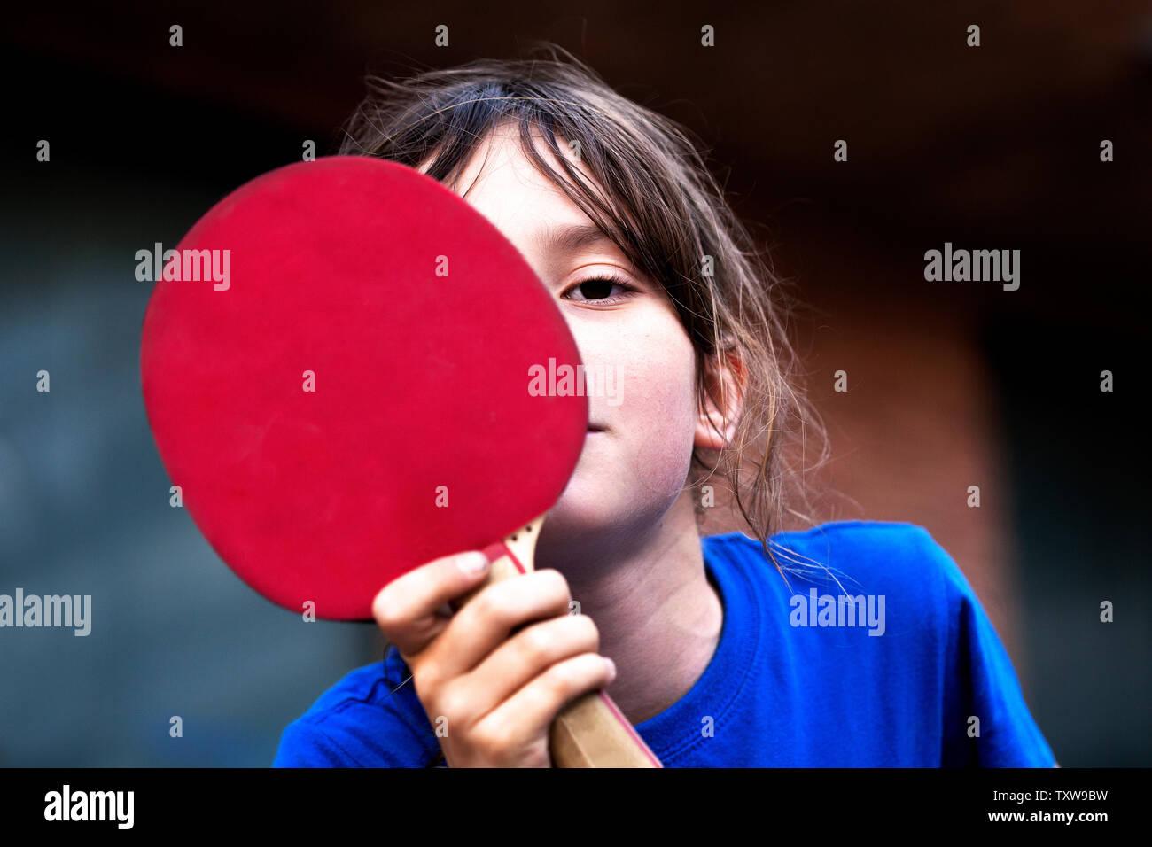 Junge versteckt sein Gesicht hinter Tischtennis bat. Stockfoto