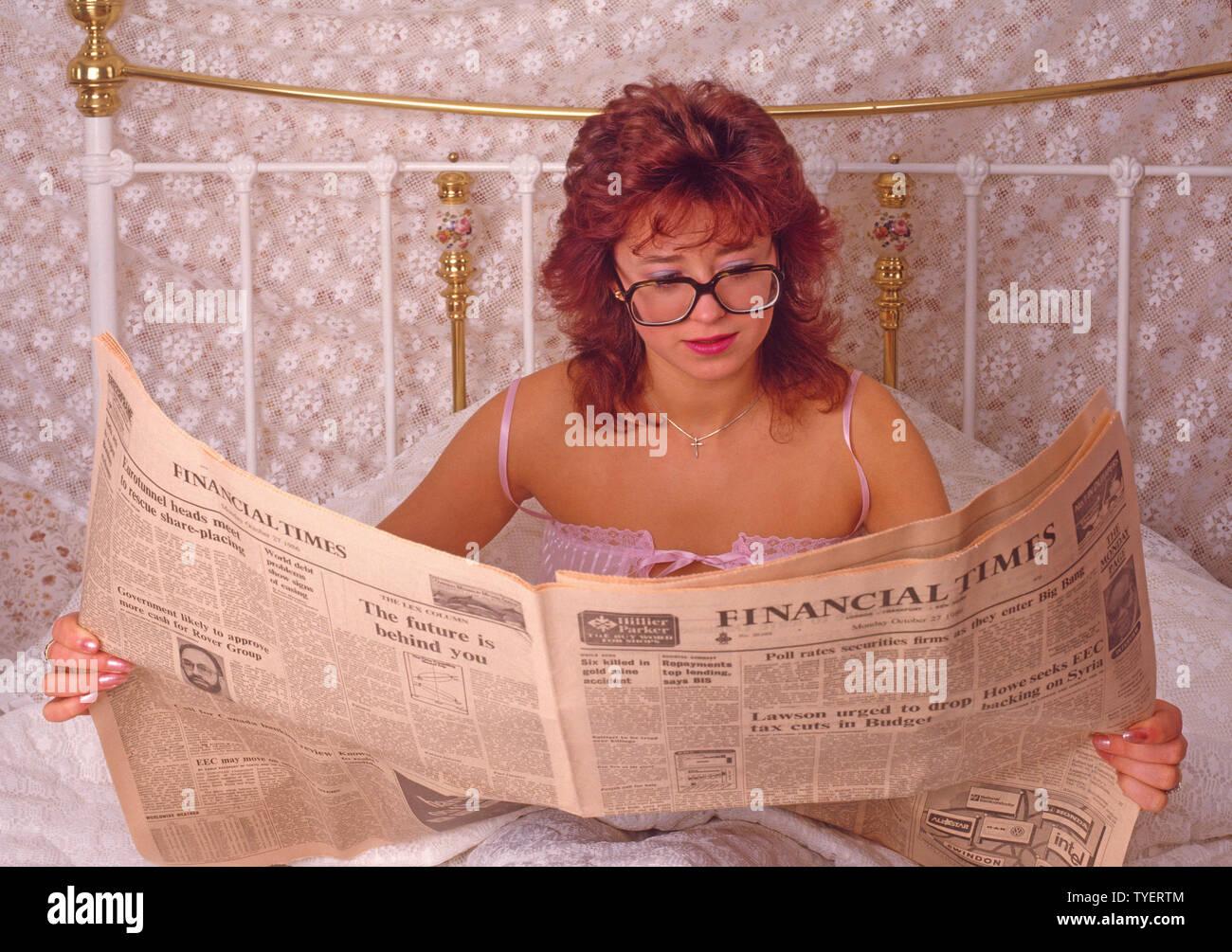 Young Business Frau Brille wieder zum Bett und liest 27. Oktober Ausgabe 1986 der Financial Times, bevor er für Arbeit Archiv 1980 s Stockbild