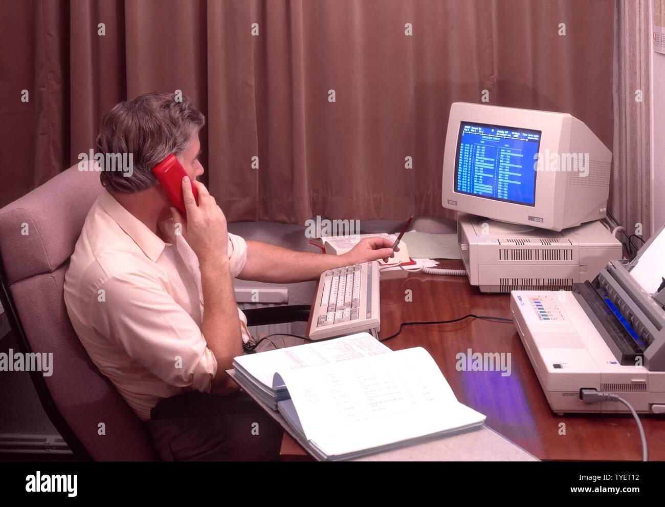 Man Selbständige im Büro am Schreibtisch sitzen, von zu Hause aus arbeiten mit Phone Amstrad desk top Computer, Bildschirm und Drucker Archiv 1980s England Großbritannien Stockbild
