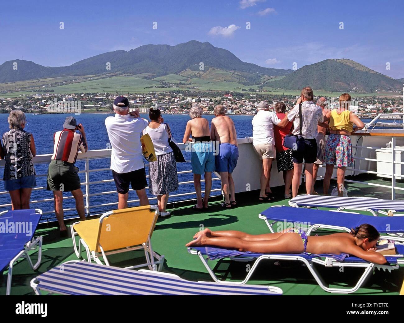 1990 s Frau Sonnenbaden & Paare Futter Geländer auf Kreuzfahrtschiff liner deck Fotos von Basseterre Küste Landschaft Karibikinsel St. Kitts Stockbild