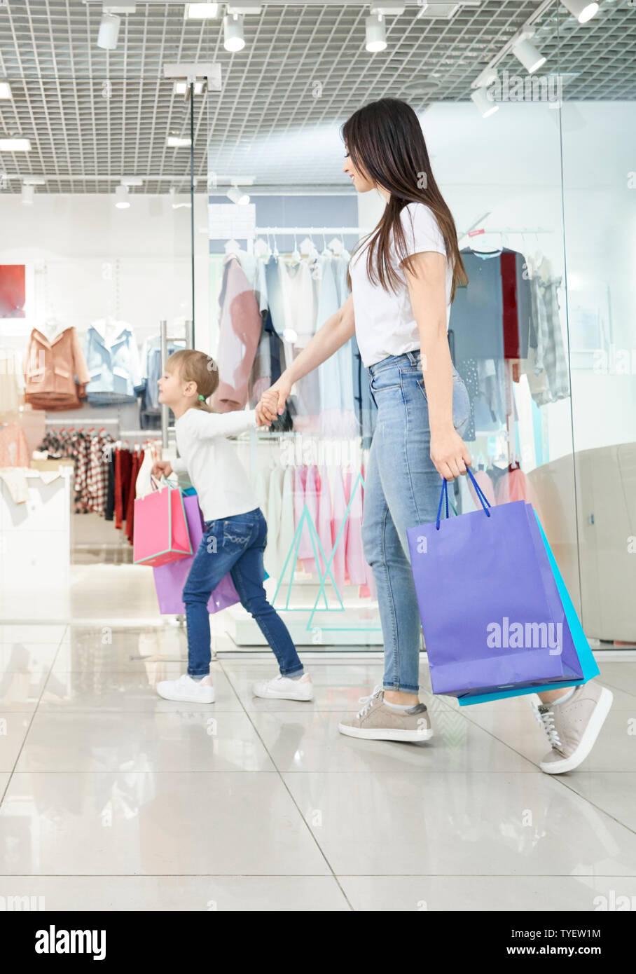 Seitenansicht der jungen attraktiven Mutter zusammen einkaufen mit kleiner Tochter in der Mall. Positive Mädchen die Hand der Frau und in Geschäften. Familie die Auswahl und Kauf neuer Kleidung und Spielzeug. Stockfoto