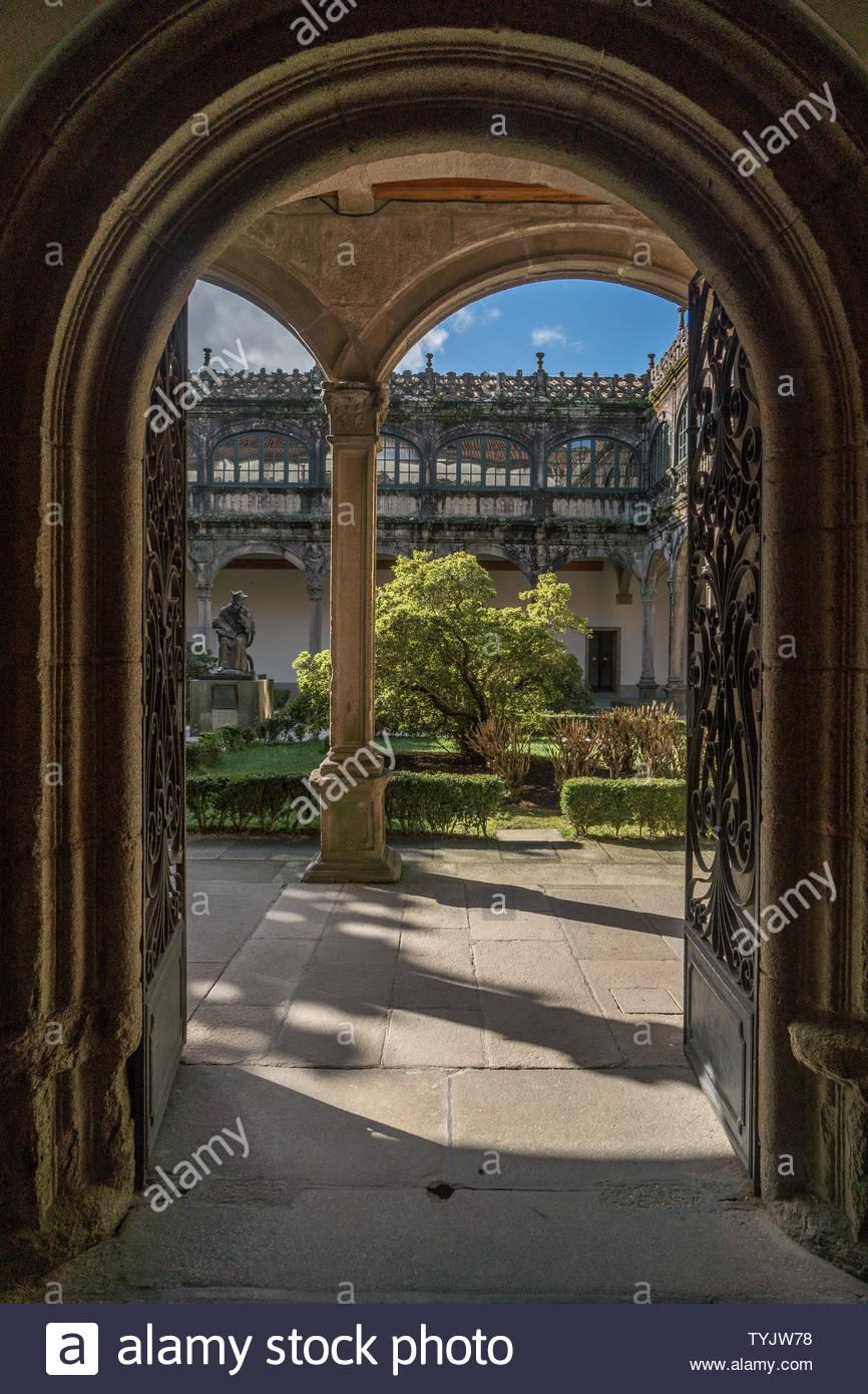 In einem zentralen Innenhof, der durch eine gewölbte Eingang über weitere Bögen um einen Gehweg mit einem grünen Garten mit Bäumen, Blumen und Form Stockbild