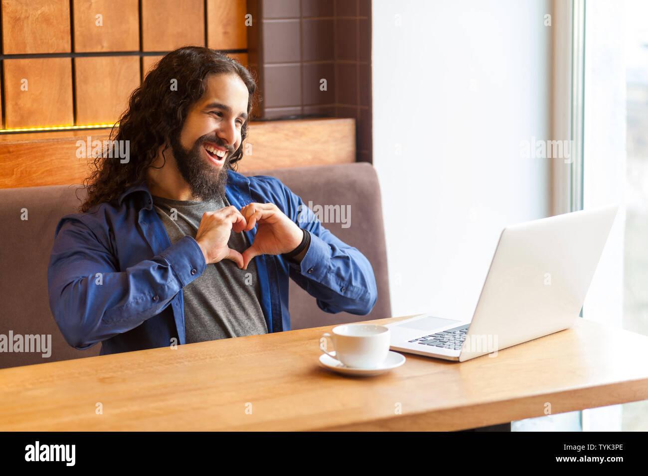 Liebe Dich! Portrait von Romantik hübscher junger erwachsener Mann Freiberufler in lässigen Stil sitzt im Cafe und im Gespräch mit seinem Freund in Laptop, Anzeigen hören Stockbild