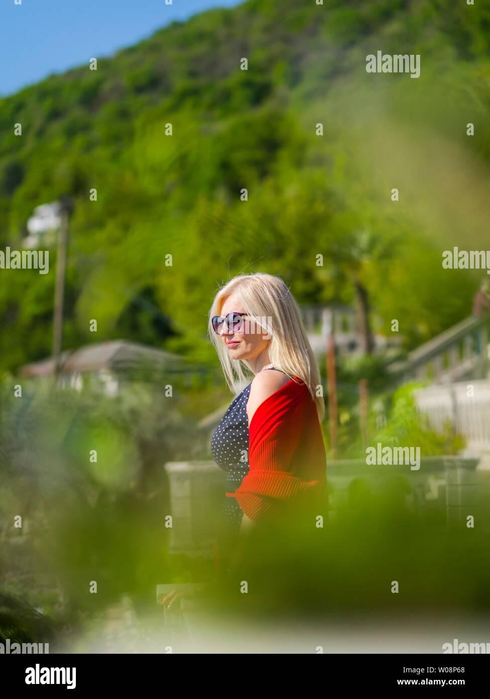Attraktive blonde Frau in natürlicher Umgebung Mitte Tag Sonne Sonnenlicht schweren Weg schauen Stockbild