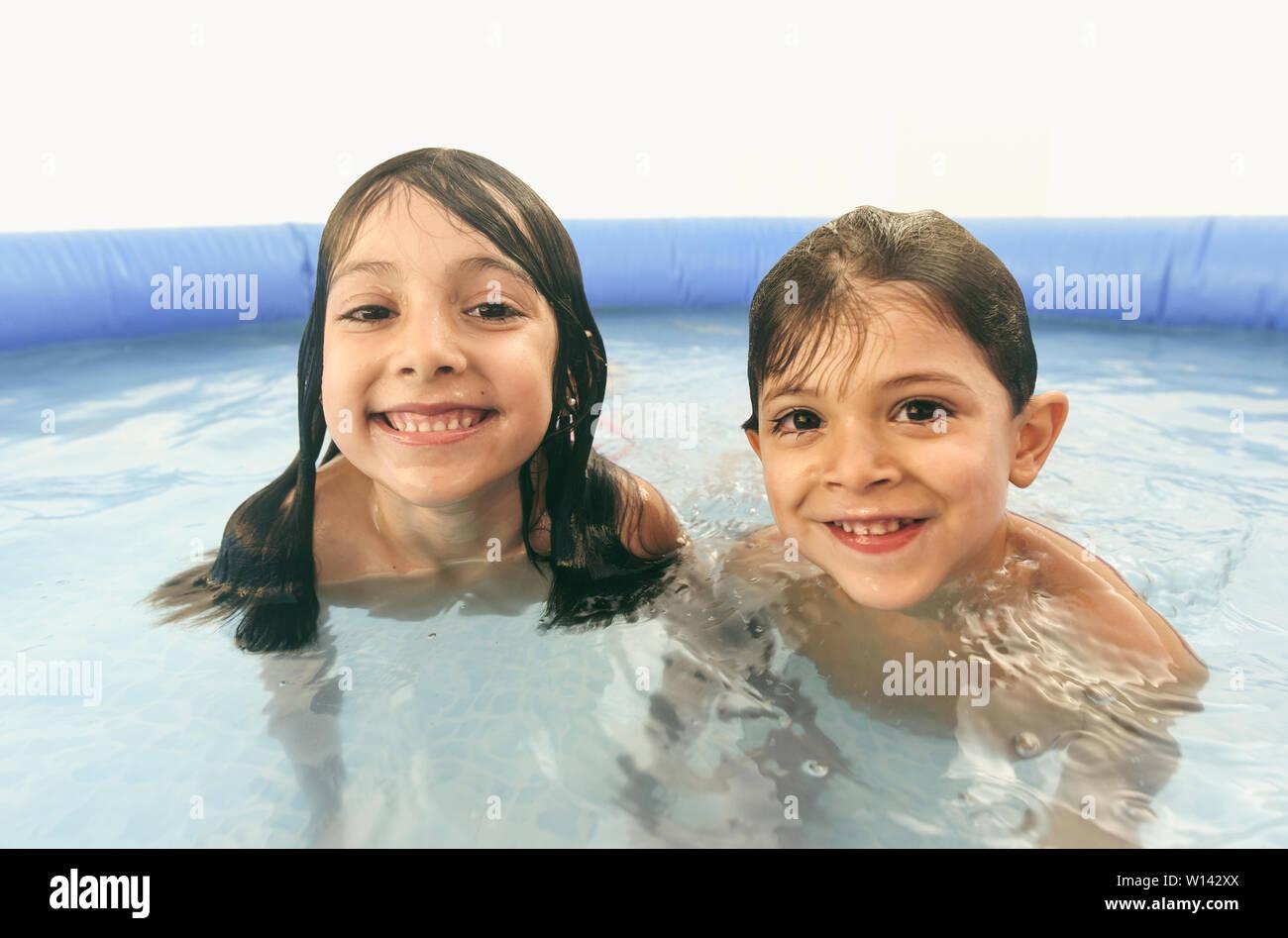 Geschwister spielen in Kunststoff Swimmingpool Kamera suchen Stockfoto