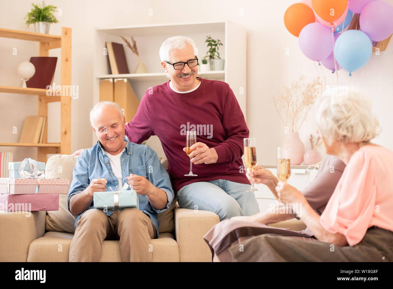 Zwei glückliche älterer Menschen und ihre Frauen mit Flöten Champagner genießen Home Party Stockbild