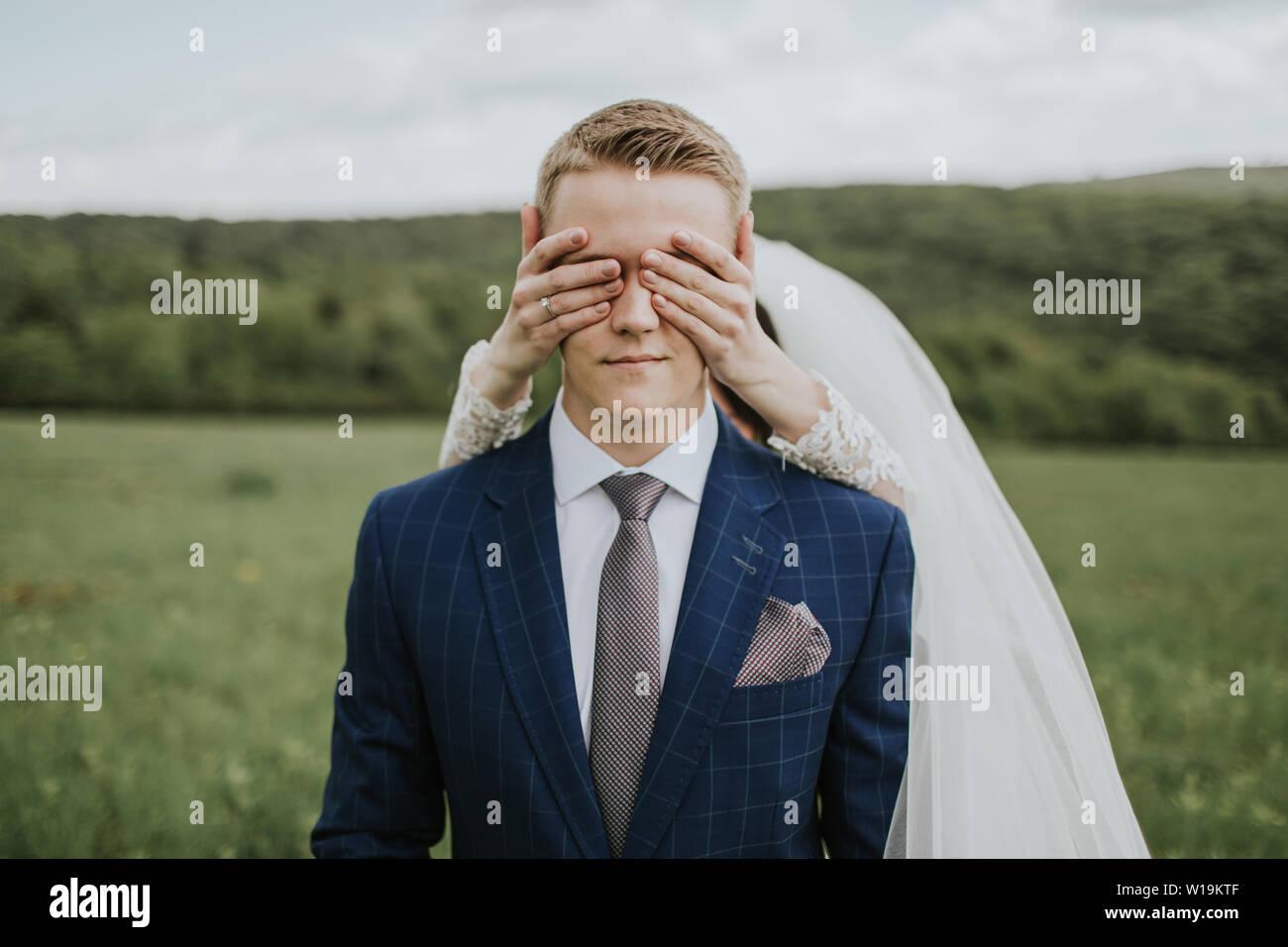 Braut, die Augen des Bräutigams. Portrait der junge Bräutigam wartet auf Wiese und Braut, die hinter ihm stehen, die seine Augen. Stockfoto