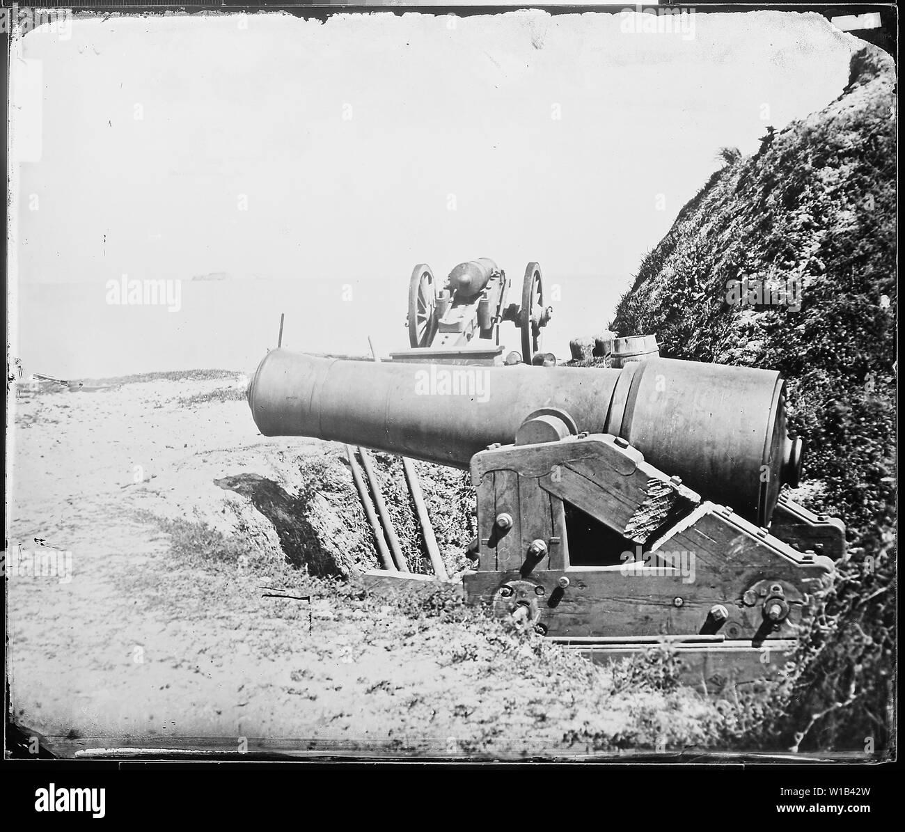 Große Pistolen in der Nähe von Ft. Sumter, S. C. Die Vordergrund Waffe ist ein 10-Zoll Modell 1844 columbiad, gebändert und geplündert, die vor kurzem von der Union am Fort Johnson in Charleston Harbor erfasst. Der Schlitten hat durch die von den Eidgenossen geschnitten worden mit der Waffe an die Union zu verweigern. Stockfoto