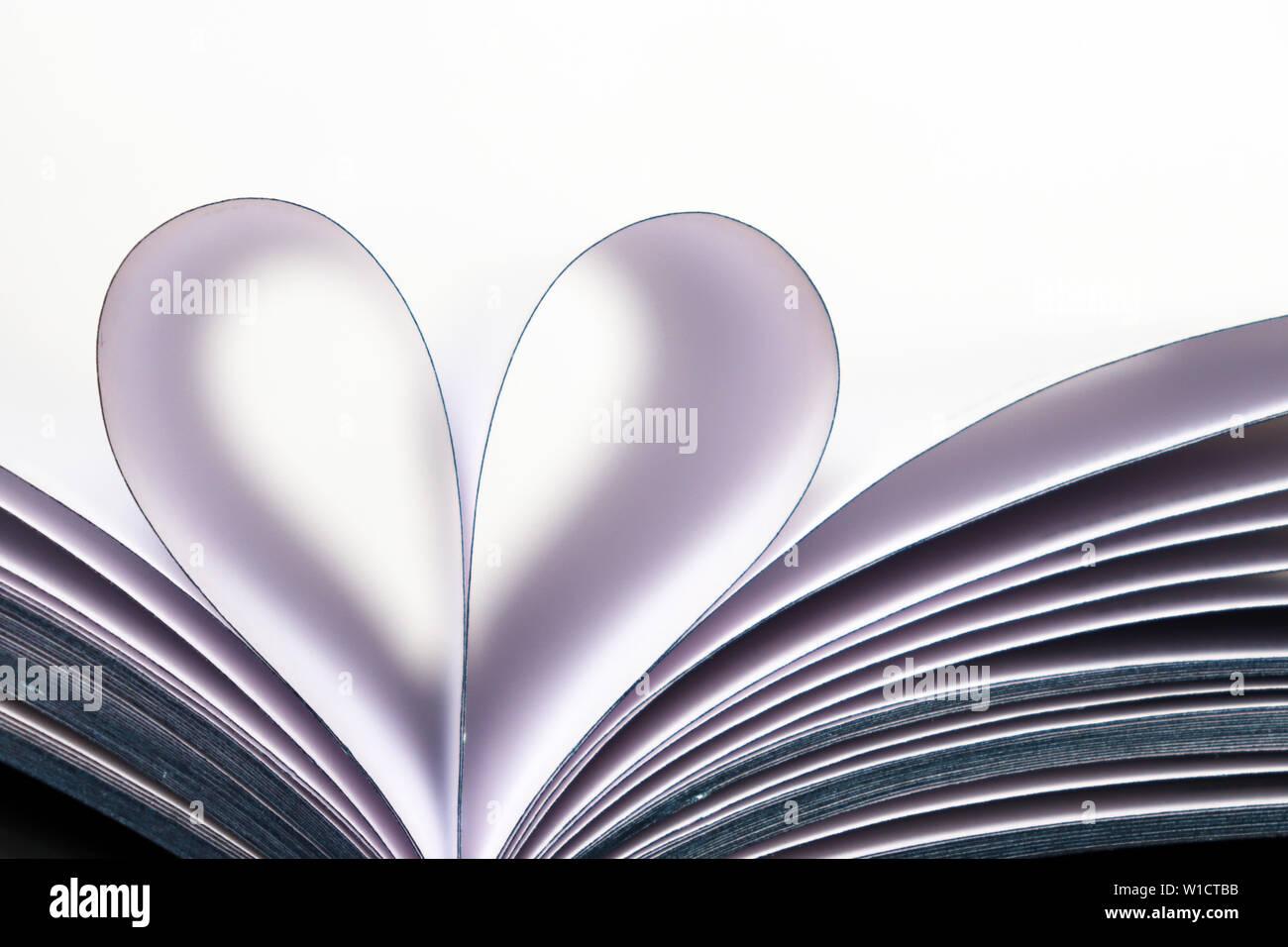 Buchen Sie Seiten geöffnet, in Herzform auf weißem Hintergrund. Liebe zum Lesen, Begriff der Wissenschaft, lernen, Romantik Stockfoto