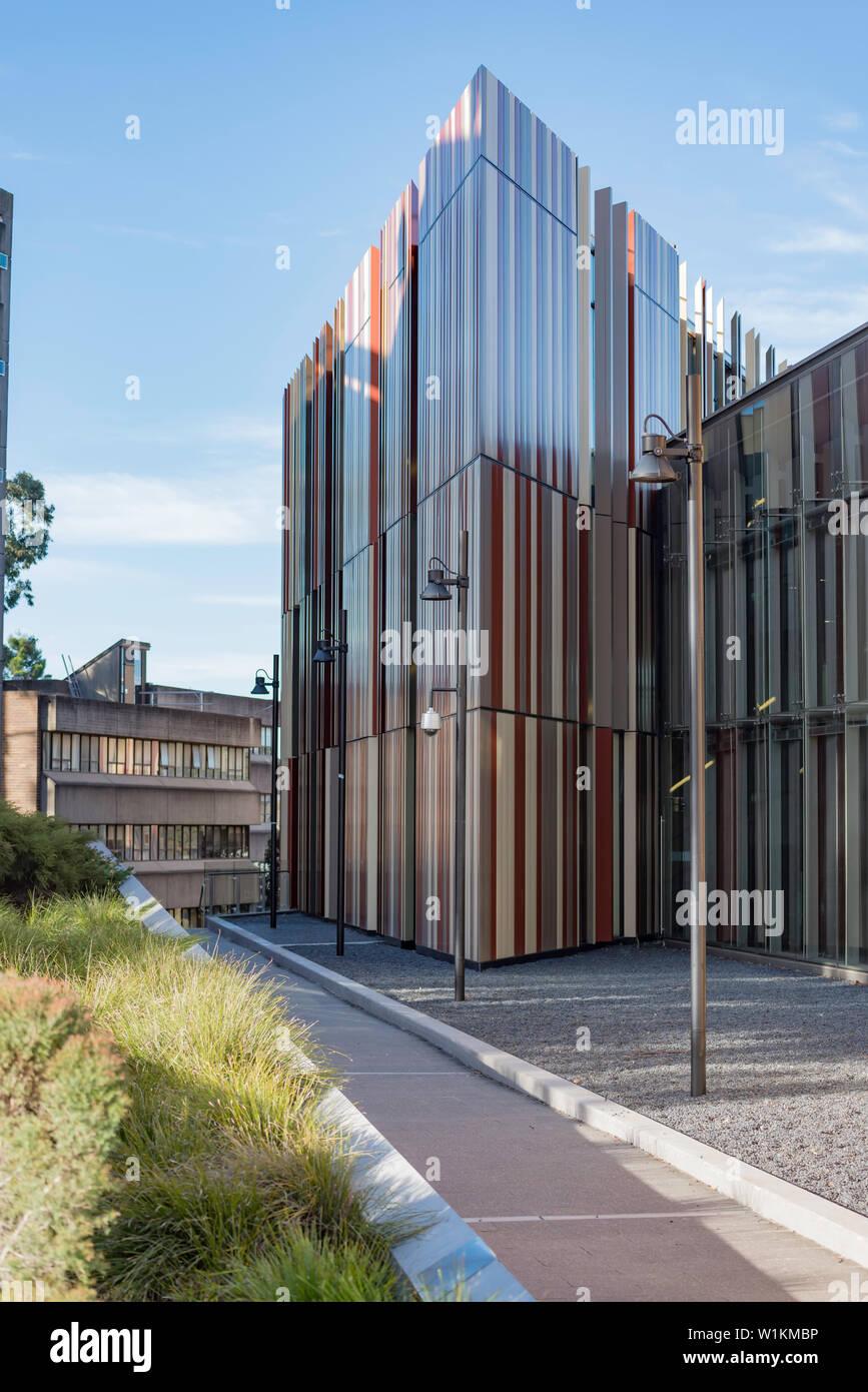Einem seitlichen Winkel Blick auf das neue Gebäude der Universitätsbibliothek an der Macquarie University in Sydney, Australien, seine Farben repräsentieren die lokalen spotted Gum Trees. Stockbild