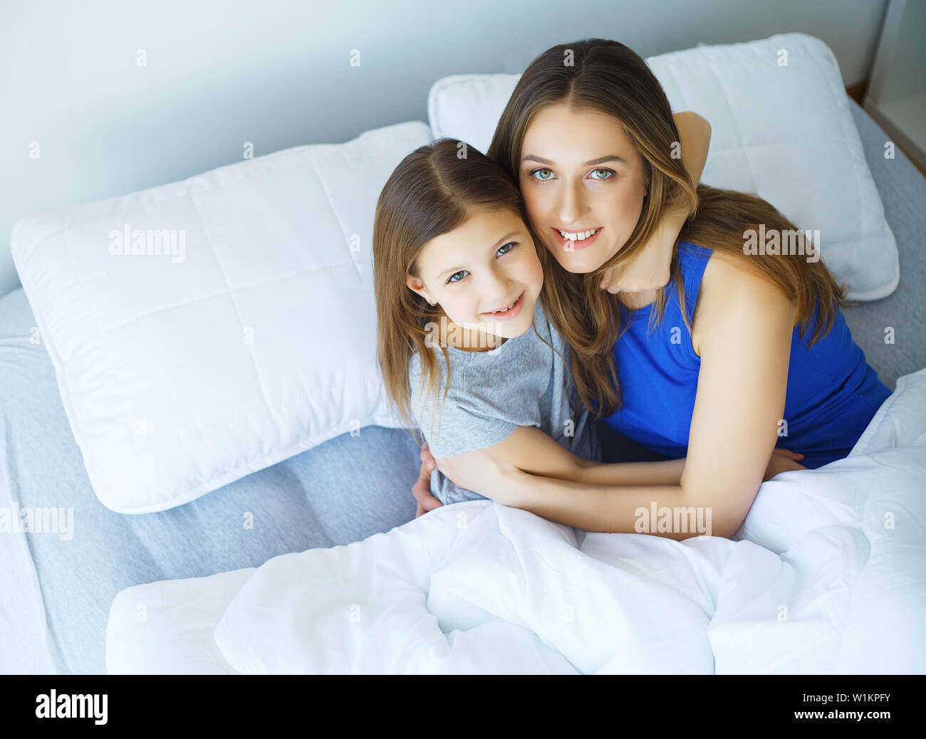 Frau und junge Mädchen im Bett lächelnd liegend Stockfoto