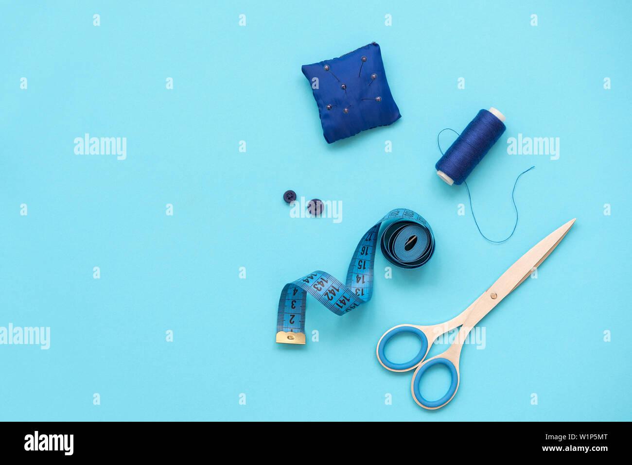 Nähzubehör mit Gewinde, Schere, Stifte, Stoff, Knöpfe und nähen Tape auf blauem Hintergrund. Ansicht von oben. Flach. Stockfoto