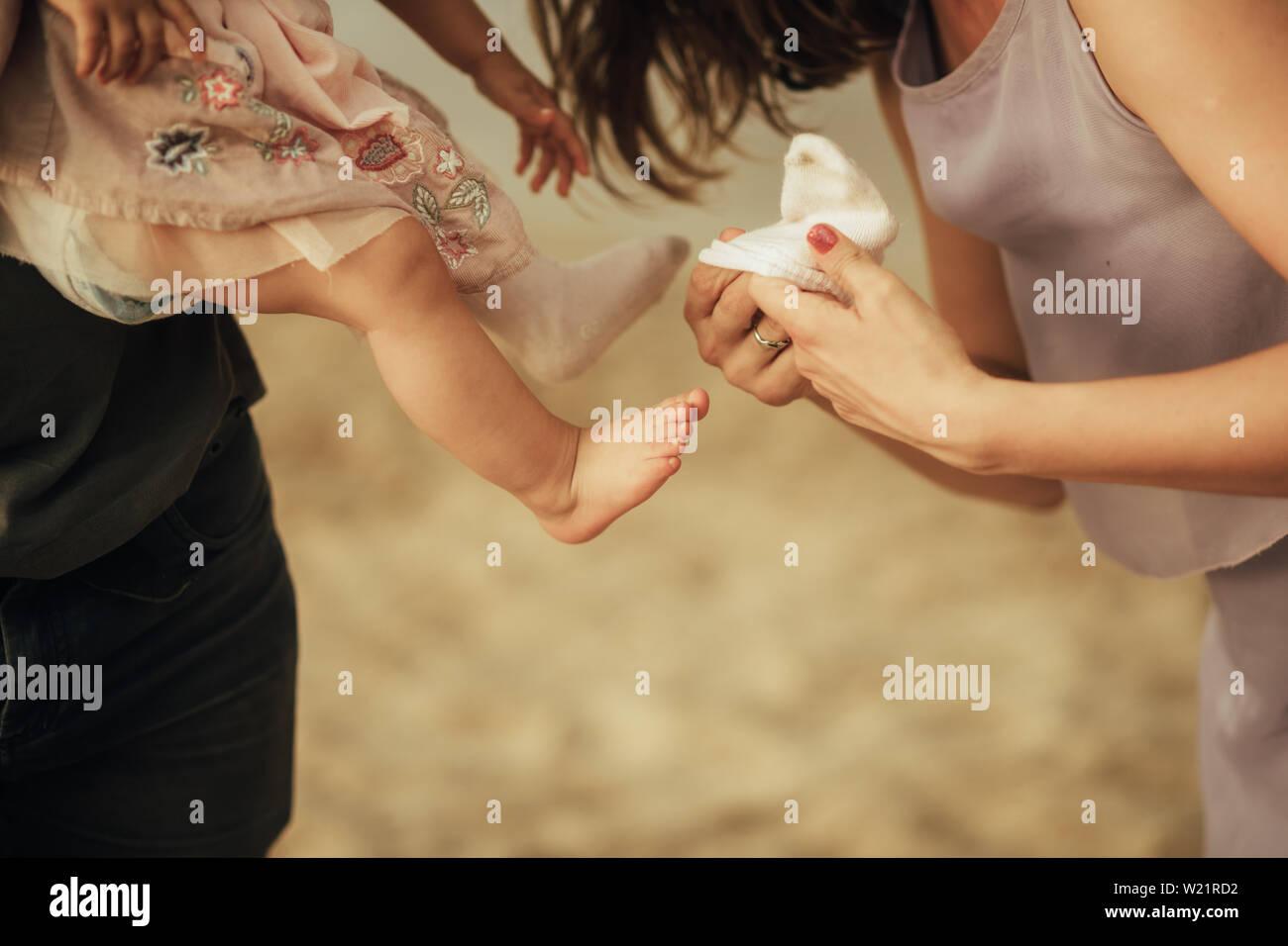 Mutter setzt eine Socke auf dem Fuß ihrer kleinen Tochter. Nahaufnahme. Stockfoto