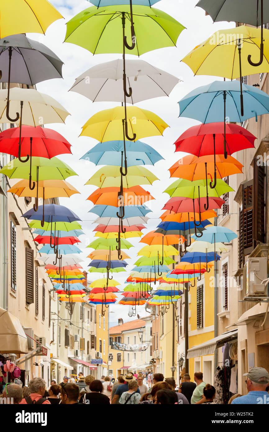Novigrad, Istrien, Kroatien, Europa - 3. September 2017 - die Touristen zu Fuß durch eine Gasse mit bunten Sonnenschirmen oben Stockfoto