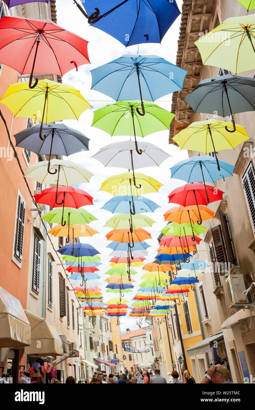 Novigrad, Istrien, Kroatien, Europa - 3. SEPTEMBER 2017 - Einheimische und Touristen zu Fuß durch unter bunten Sonnenschirmen Stockfoto