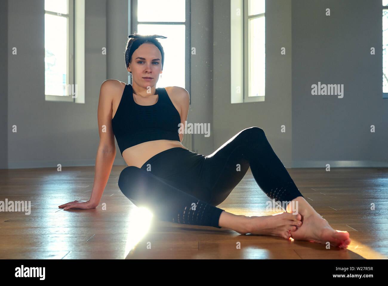 Eine Frau übt Yoga im Fitnessraum in der Morgendämmerung. Konzentration, strahlender Sonnenschein, Stretching, gesunden Lebensstil. Stockbild