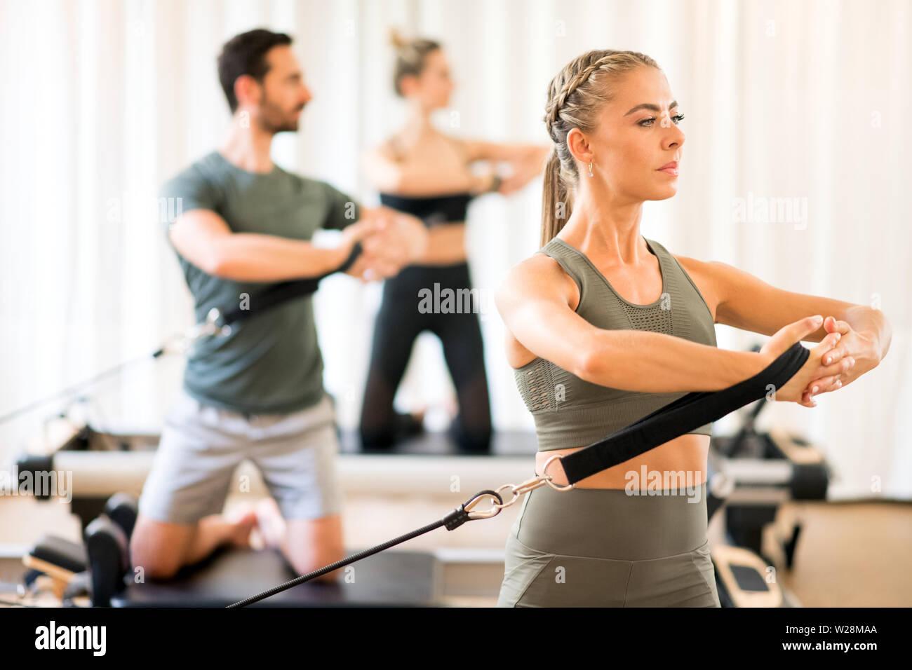 Frau mit Menschen in Fortbildung Torso Rotation mit Hilfe von Geräten im Fitnessstudio Stockbild