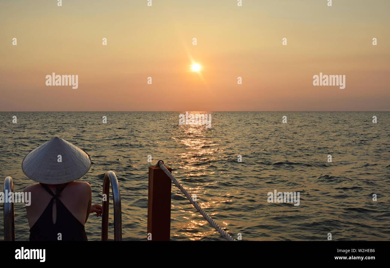 Junge attraktive Frau an der Küste in Vietnam das Tragen eines typischen hat bei den Sonnenuntergang starrte. Junge Dame gerade Sonnenuntergang über dem Südchinesischen Meer im Pier. Stockfoto