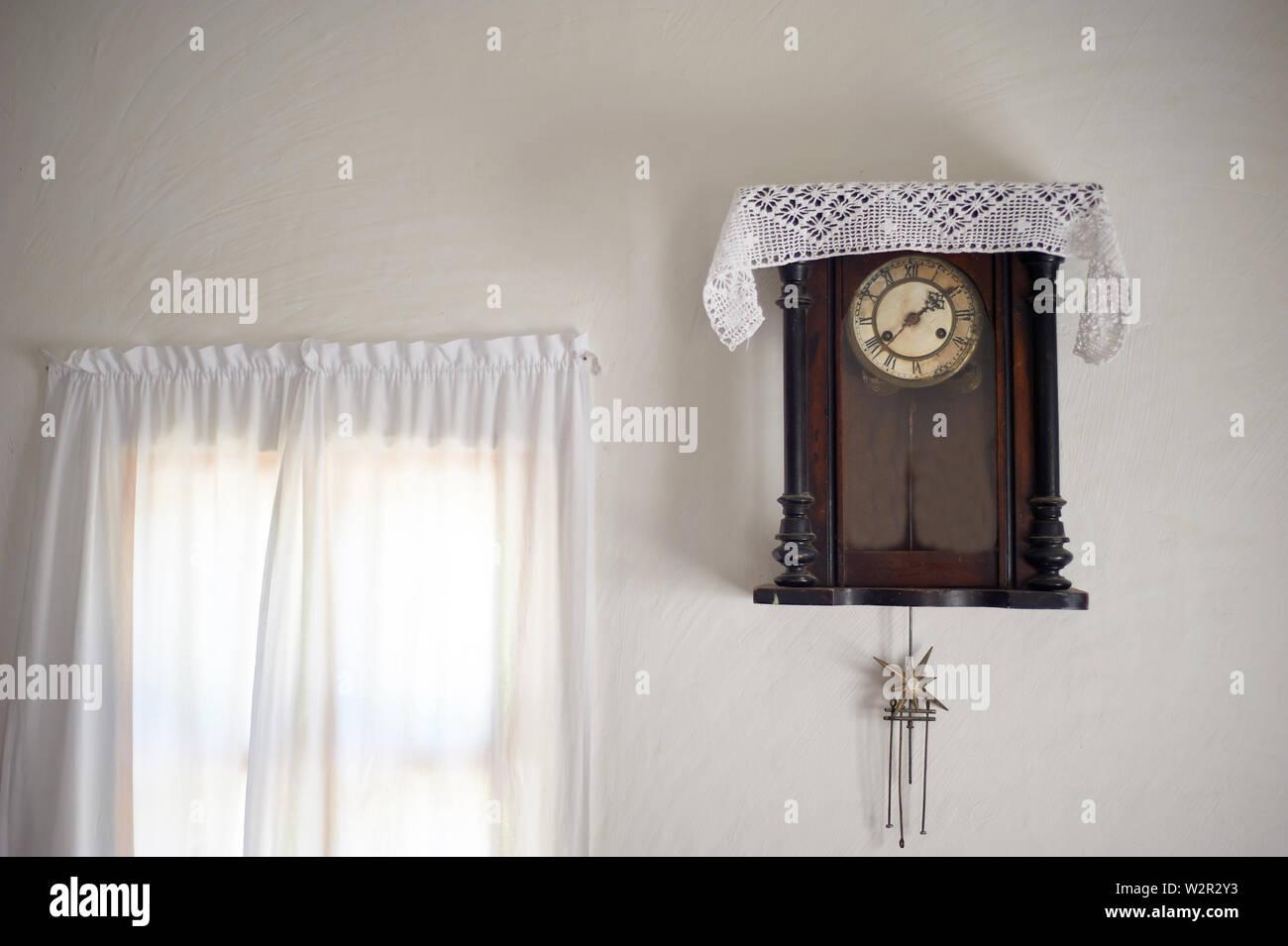 Eine alte Wanduhr mit einer Serviette abgedeckt. Weißes Leinen Vorhang. . Retro Stockfoto