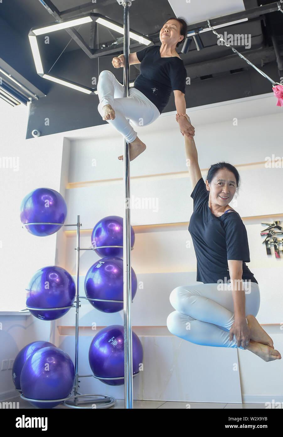"""(190711) - JILIN, Juli 11, 2019 (Xinhua) - Jiang Zhijun (oben) und Li Fengmei Praxis Pole Dancing im Tanzsaal in Jilin Stadt, im Nordosten Chinas in der Provinz Jilin, 10. Juli 2019. Eine Gruppe von Dama, was sich auf die Legionen von meist im mittleren Alter Frauen, bildeten ein Team von Pole Dancing in Jinlin Stadt, im Nordosten Chinas in der Provinz Jilin im Jahr 2016. Die Mannschaft hat acht Mitglieder mit einem Durchschnittsalter von 64. """"Pole Dancing für seine Weichheit und Stärke bekannt ist, sagt Jiang Zhijun, der 68-jährige Teamleiter."""" Wir begannen mit grundlegenden Krafttraining, ging dann nach vorn high-level bewegt sich schrittweise."""". Stockfoto"""