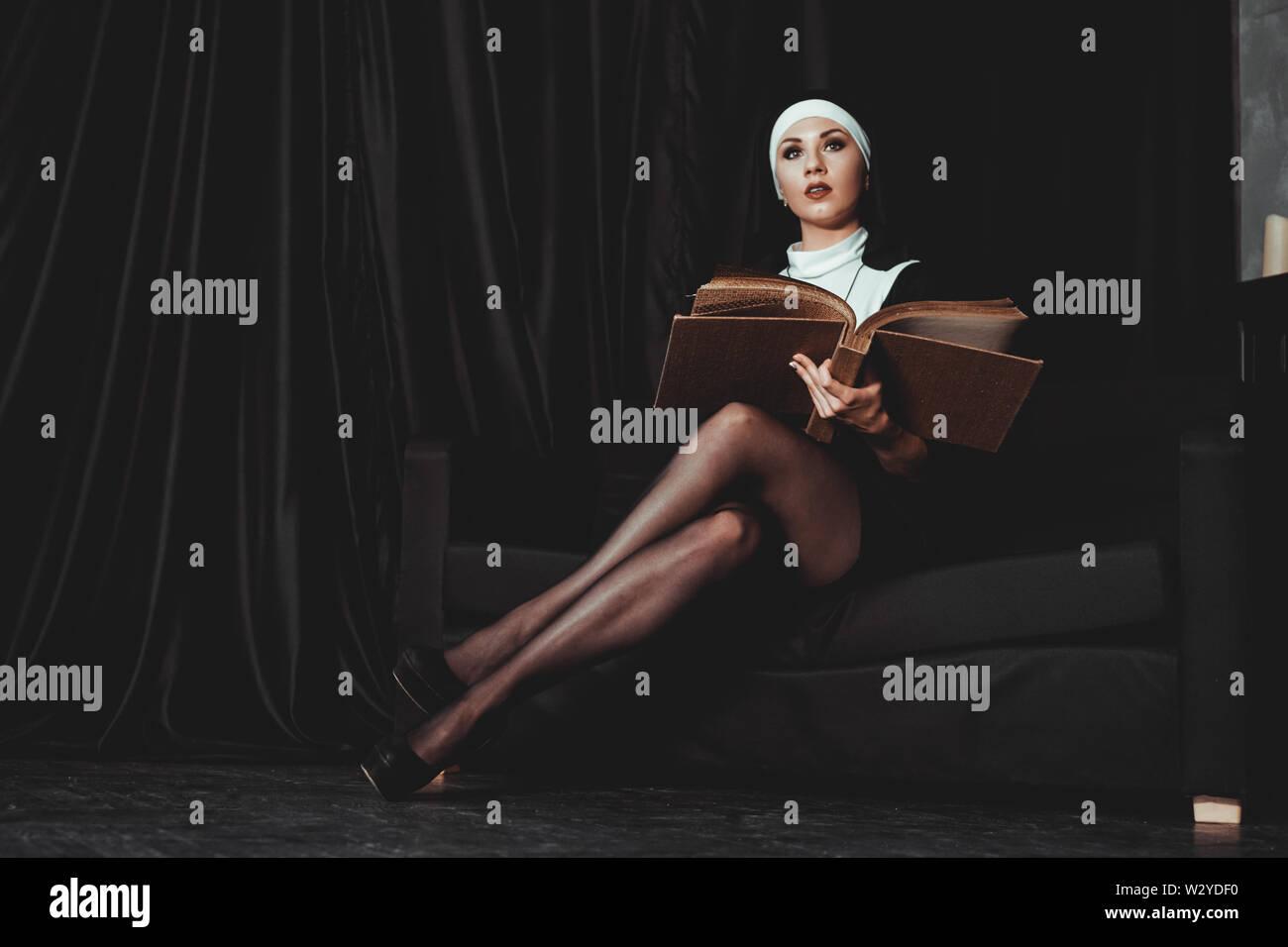 Schöne junge Nonne in Religion schwarzen Anzug hält Bibel und auf Kamera posieren mit großen Buch auf einem schwarzen Hintergrund. Religion Konzept. Stockfoto