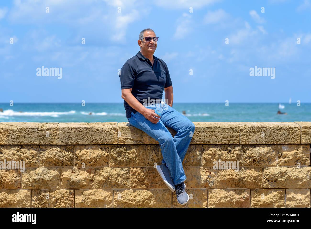 Lächelnd trendy Touristische älterer Mann sitzt von alten Ziegel historische Stein. Portrait von Stattlichen alter Mode Senior mit schwarzen T-Shirt und Jeans auf Bl Stockbild