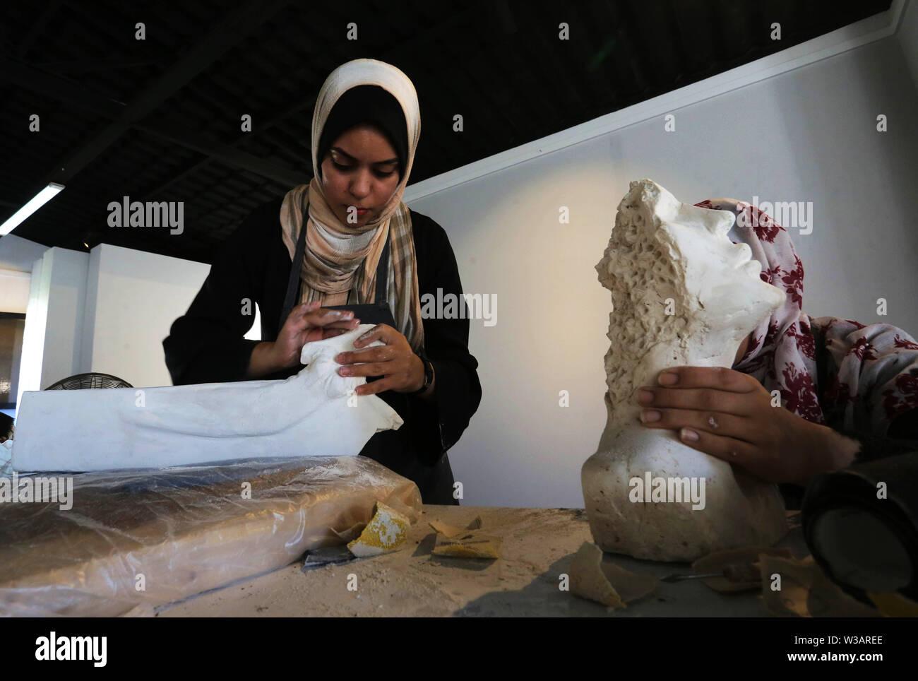 Gaza, Gazastreifen, palästinensischen Gebiet. 13. Juli, 2019. Palästinensische Künstler machen Ton Skulpturen während einer Schulung Workshop bei Shababek für Zentrum für zeitgenössische Kunst, in Gaza, den 13. Juli 2019. Die Lehrwerkstatt finanziert durch die Arabischen Fonds für Kunst und Kultur (Afac) zielt darauf ab, die Fähigkeiten der devolop junge Künstler mit modernen Werkzeugen und Materialien Quelle: Ashraf Amra/APA-Images/ZUMA Draht/Alamy leben Nachrichten Stockbild
