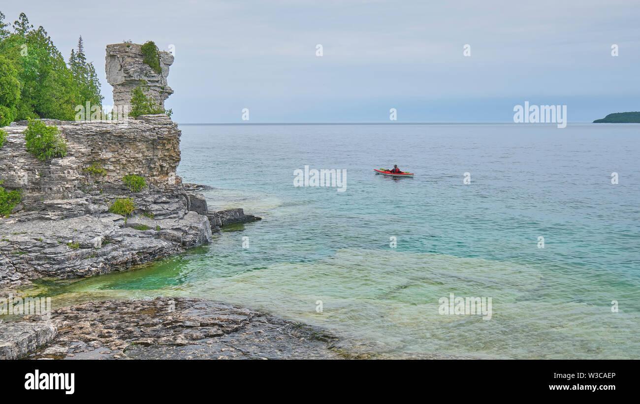 Lone kayaker paddeln Vergangenheit eines der geologische Formation auf Blumentopf Insel Georgian Bay Ontario. Stockbild