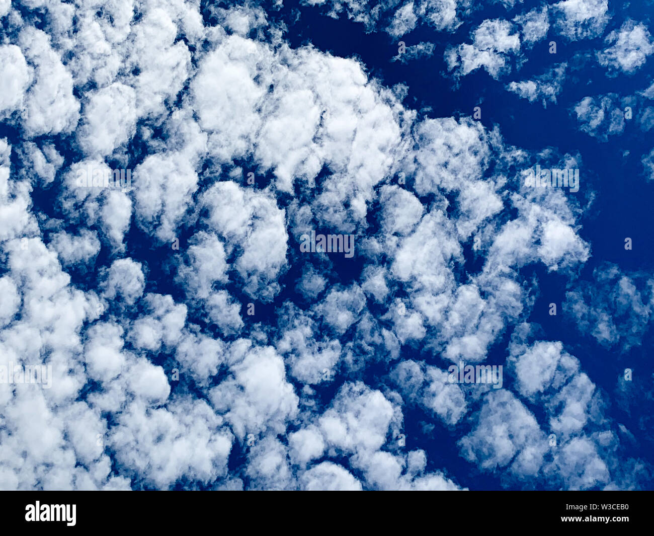 - Wolken sind Kleine abgerundete Puffs, die in der Regel in langen Reihen hoch am Himmel erscheinen. - Sind in der Regel weiß, aber manchmal erscheinen gra Stockbild