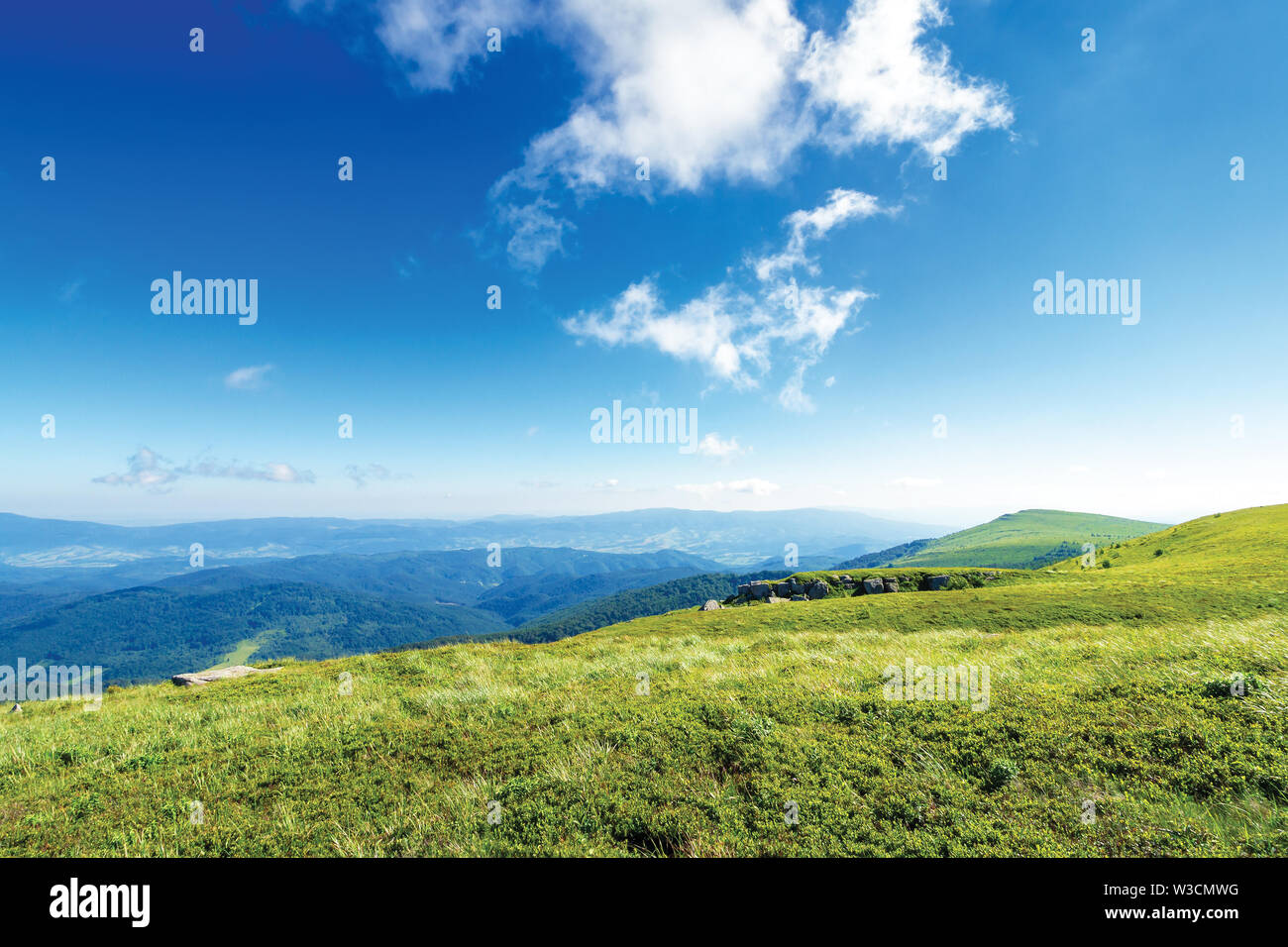 Schönen Sommer Landschaft in den Bergen., grünen Wiesen, Felsen und Gipfel in der Ferne. interessante Wolkenbildung auf der blauen Himmel. ridge in der d Stockbild