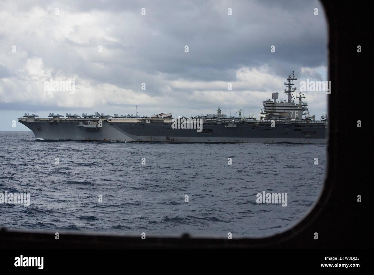 Der Nimitz-Klasse Flugzeugträger USS Ronald Reagan (CVN 76) die Durchfuhr durch die Tasmanische See, die sich in der Ausbildung neben den Amphibisches Schiff USS Wasp (LL 1), Juli 11, 2019 als Teil der Talisman Sabre 2019. Wasp, Flaggschiff der Wasp Expeditionary Strike Group, mit Eingeschifft 31 MEU, nimmt derzeit an Talisman Sabre 2019 vor der Küste im Norden von Australien. Eine bilaterale, Biennale, Talisman Sabre ist für US-amerikanische und australische Combat Training, Bereitschaft und Interoperabilität durch realistische, einschlägige Ausbildung notwendig, regionale Sicherheit, Friedens- und Sta zu erhalten zu verbessern. Stockbild