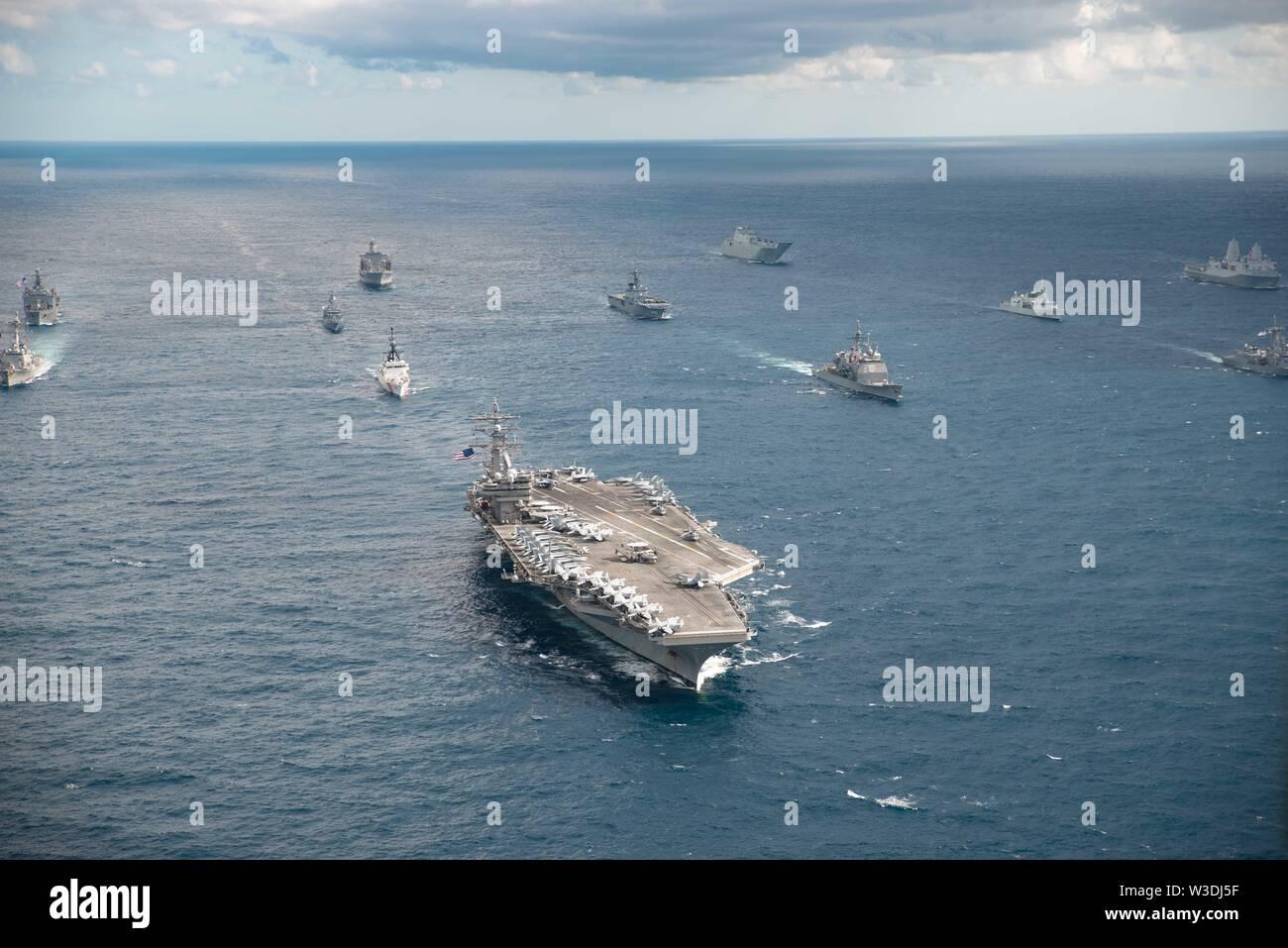 190711-N-RF 825-1213 CORAL SEA (11. Juli 2019) Die US-Marine Flugzeugträger der Nimitz-Klasse USS Ronald Reagan (CVN 76) führt eine Bildung von 17 andere Schiffe der US Navy, US Coast Guard, der Royal Australian Navy, Royal Canadian Navy und Japan Maritime Verteidigung-kraft (JMSDF) während der Talisman Sabre 2019. Talisman Sabre 2019 zeigt die Nähe des australischen und US-amerikanischen Allianz und die Stärke der militärischen Beziehung. Dies ist der achte Iteration dieser Übung. (U.S. Marine Foto von Mass Communication Specialist 3. Klasse Jason Tarleton/Freigegeben) Stockbild