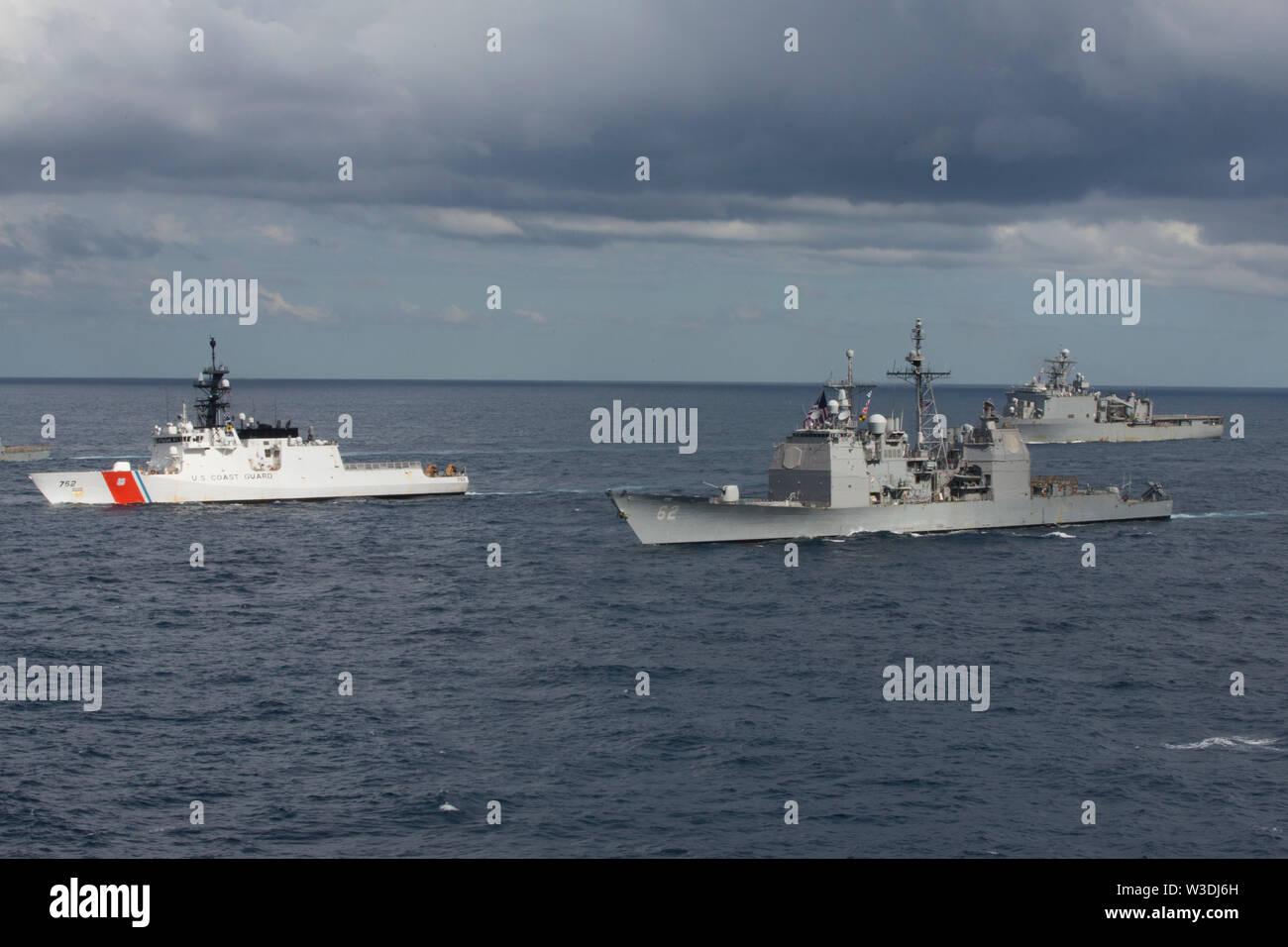 Schiffe der Expeditionary Strike Group 7 Transit durch die Tasmanische See, die sich in der Ausbildung neben den Amphibisches Schiff USS Wasp (LL 1), Juli 11, 2019 als Teil der Talisman Sabre 2019. Wasp, Flaggschiff der Wasp Expeditionary Strike Group, mit Eingeschifft 31 MEU, nimmt derzeit an Talisman Sabre 2019 vor der Küste im Norden von Australien. Eine bilaterale, Biennale, Talisman Sabre ist für US-amerikanische und australische Combat Training, Bereitschaft und Interoperabilität durch realistische, einschlägige Ausbildung notwendigen regionalen Sicherheit, Frieden und Stabilität zu verbessern. (U.S. Marine Co Stockbild