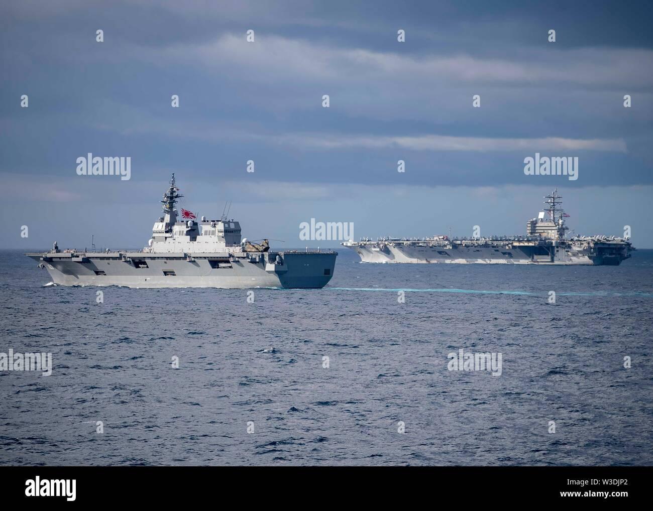 190711-N-WK 982-1215 CORAL SEA (11. Juli 2019) Die Japan Maritime Verteidigung-kraft Hy?ga-Klasse Hubschrauber Zerstörer JS Ise (DDH182), links, und der US Navy Flugzeugträger der Nimitz-Klasse USS Ronald Reagan (CVN 76) Manöver in Ausbildung während der Talisman Sabre 2019. Talisman Sabre 2019 zeigt die Nähe des australischen und US-amerikanischen Allianz und die Stärke der militärischen Beziehung. Dies ist der achte Iteration dieser Übung. (U.S. Marine Foto von Mass Communication Specialist 2. Klasse John Harris/Freigegeben) Stockbild