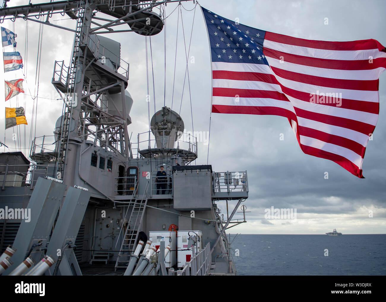 190711-N-WK 982-2110 CORAL SEA (11. Juli 2019) Die Crew der Ticonderoga-Klasse geführte-missile Cruiser USS Chancellorsville (CG62) Manöver in Formation während Talisman Sabre 2019. Talisman Sabre 2019 zeigt die Nähe des australischen und US-amerikanischen Allianz und die Stärke der militärischen Beziehung. Dies ist der achte Iteration dieser Übung. (U.S. Marine Foto von Mass Communication Specialist 2. Klasse John Harris/Freigegeben) Stockbild