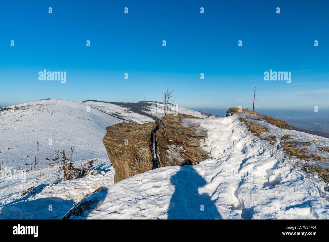 Felsbrocken auf Malinowska Skala Hügel mit Skrzyzne Hügel auf dem Hintergrund in Beskid Slaski bergen in Polen während des wnter Tag mit klaren Himmel Stockbild