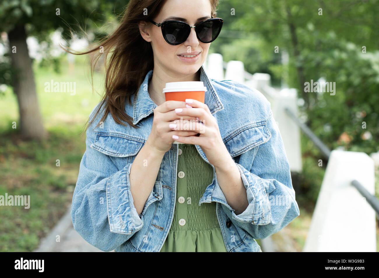 Junge Mädchen trinken Kaffee auf der Straße und zu Fuß Stockbild