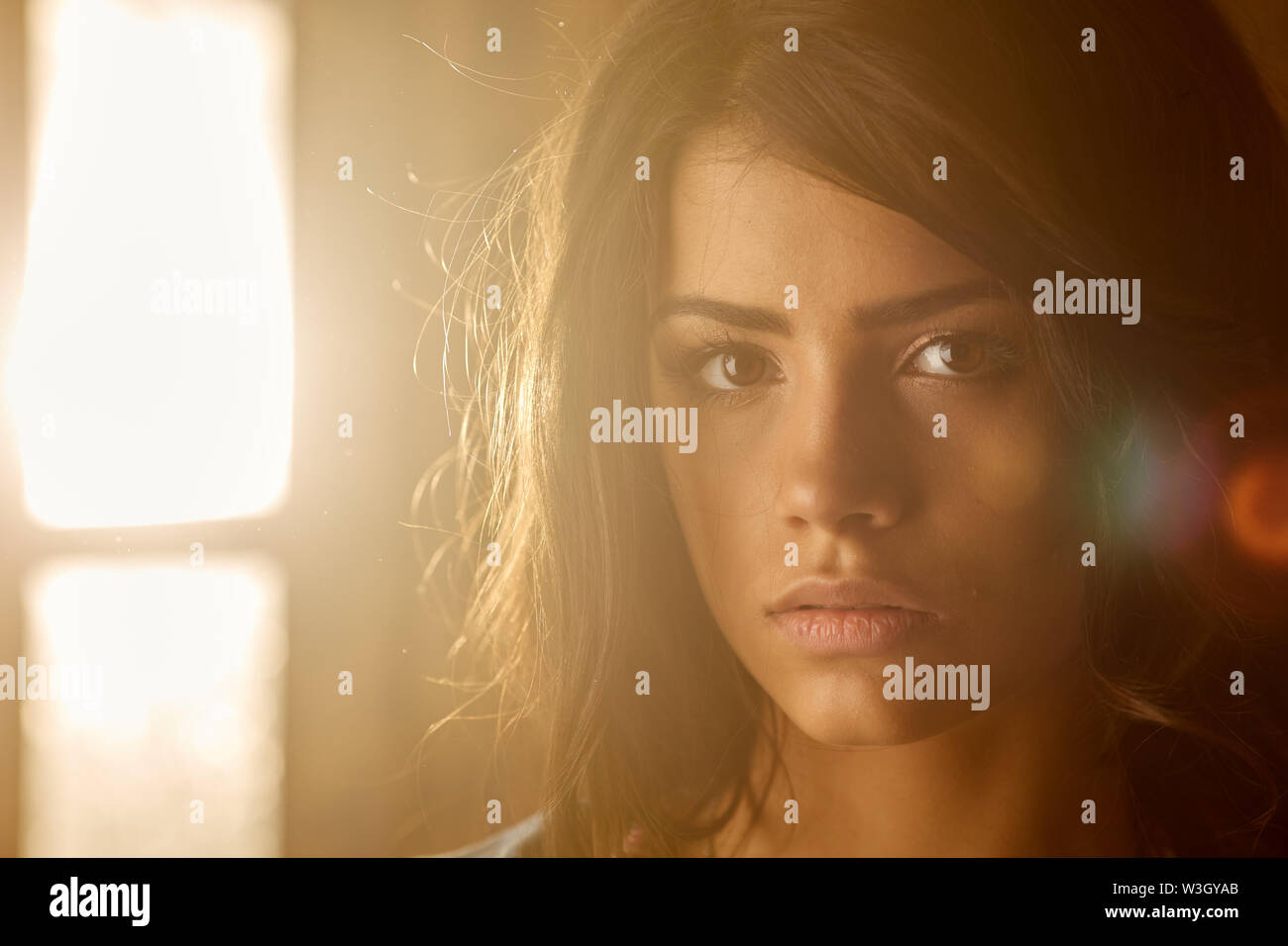 Schön trauriges Mädchen am Fenster an einem sonnigen Tag. Stockbild