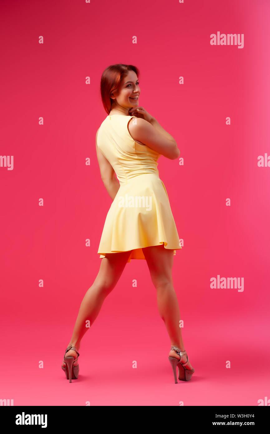 Schöne Frau mit gesunden Körper tragen in einem Kleid zu tanzen und sich zu drehen auf rosa Hintergrund. Das Konzept der Sommer mode kleidung und relaxati Stockbild