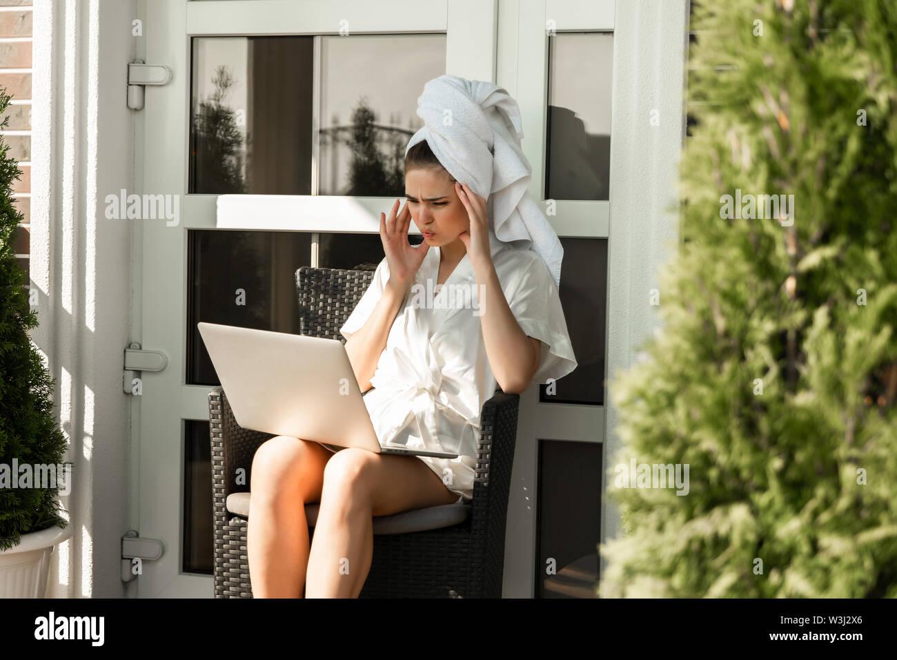 Gereizte junge brünette Frau mit Morgenmantel und weißen Handtuch in Ihrem Laptop arbeiten von zu Hause aus auf der Terrasse sitzen. Stockbild