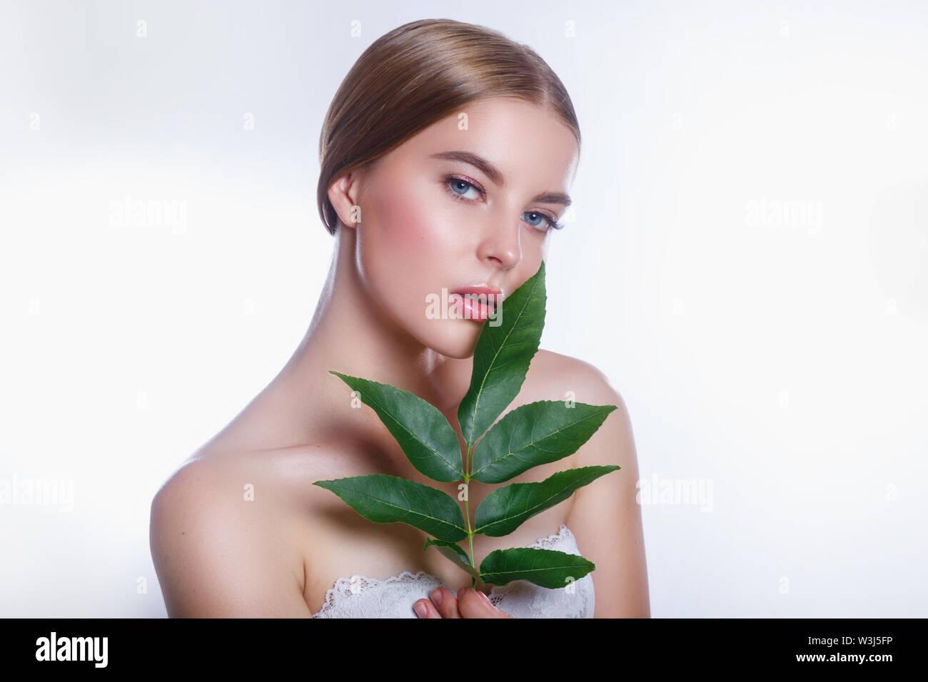 Schöne Frau Gesicht Porträt mit Green leaf Konzept für die Pflege der Haut oder organische Kosmetik auf weißem Hintergrund Stockbild