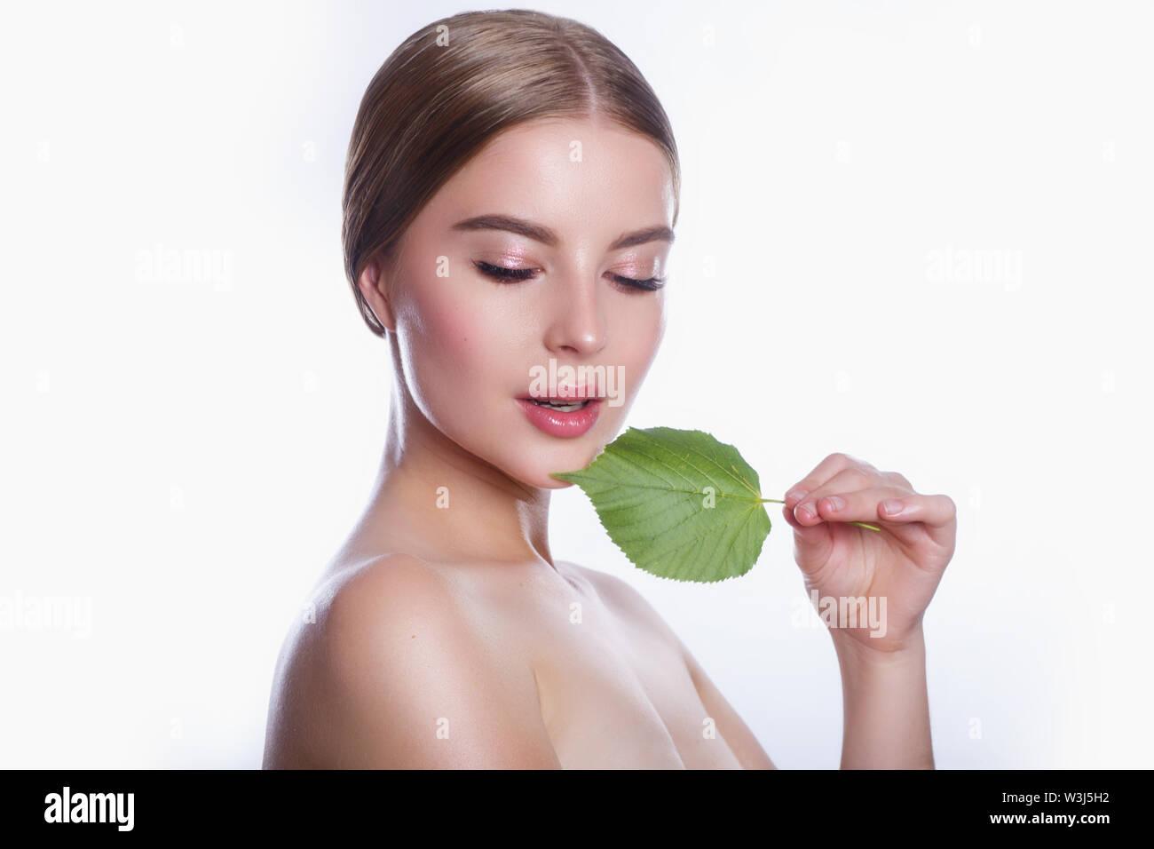Schöne junge Frau mit saubere, frische Haut und grünes Blatt auf weißem Hintergrund. Mädchen Schönheit Gesichtspflege. Gesichtsbehandlung. Stockbild