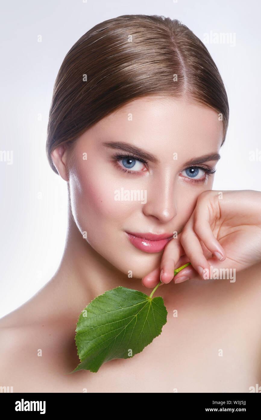 Schöne Frau Gesicht Porträt mit grünen Blättern auf weißem Hintergrund. Konzept für die Pflege der Haut oder organische Kosmetik Stockbild
