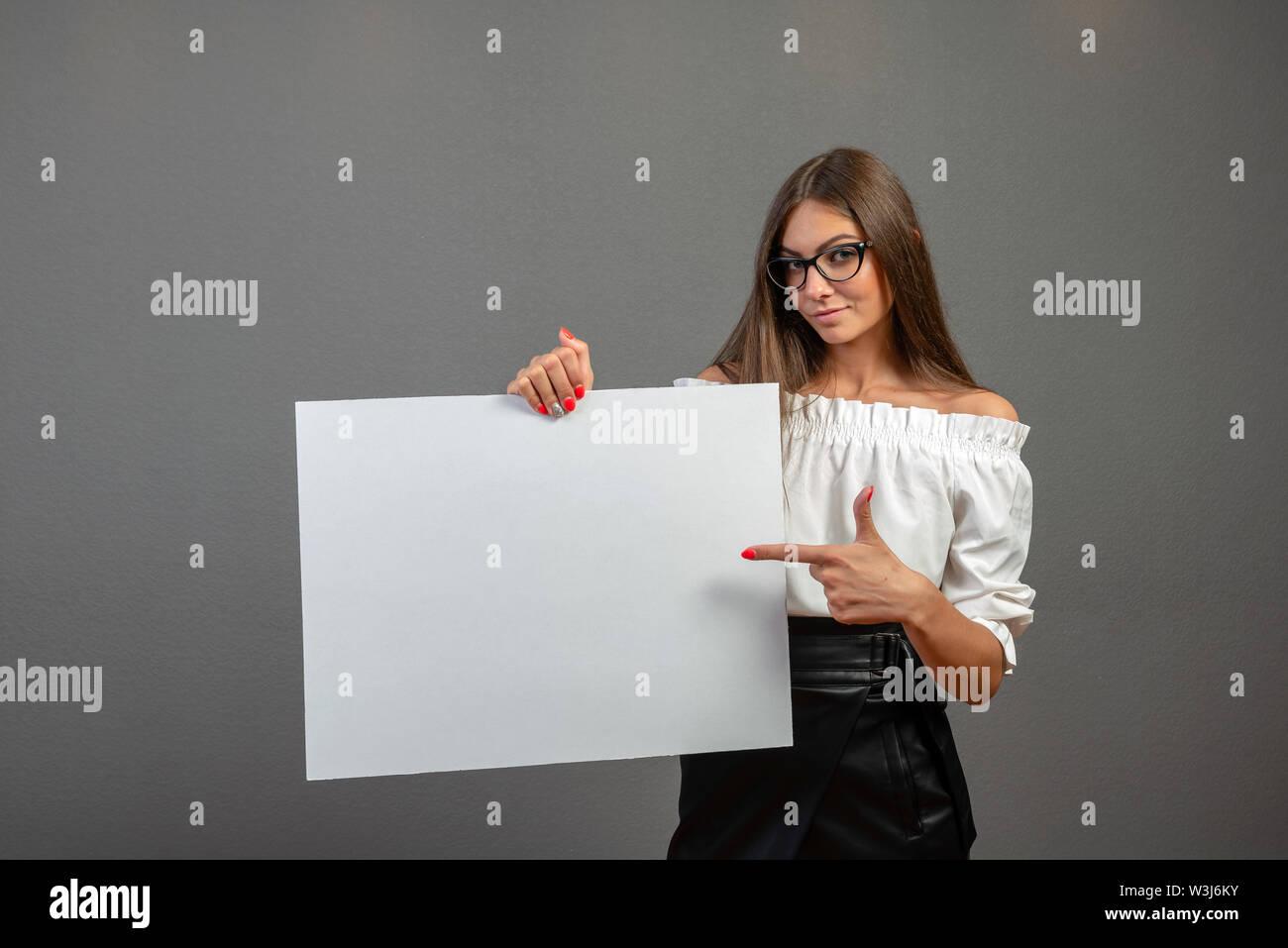 Junge lächelnde Frau an einem leeren weißen Blatt für Werbung auf einem grauen Hintergrund zeigen Stockbild