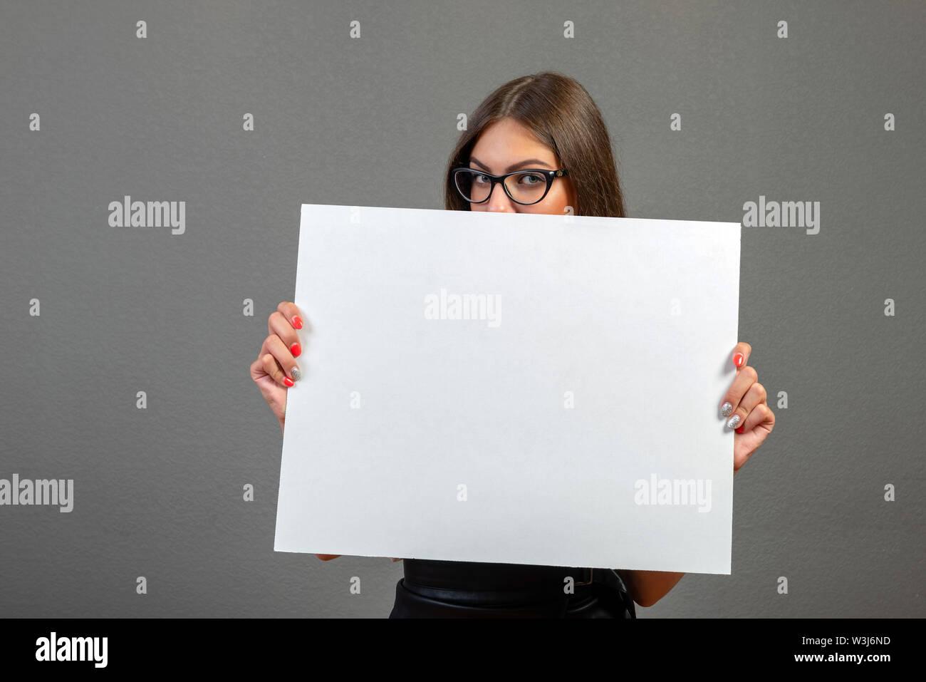 Schöne Frau mit einem leeren Plakat auf grauem Hintergrund. Stockbild