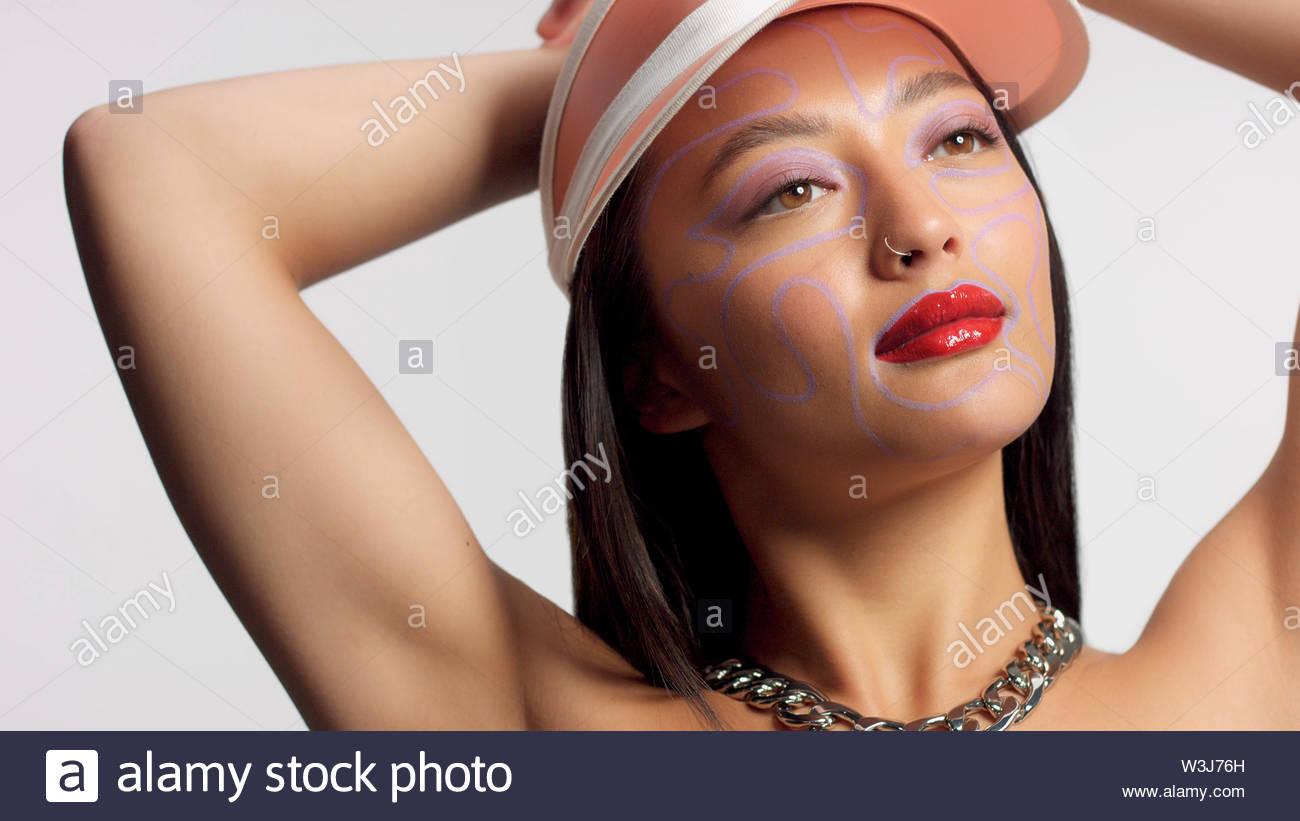 Mischlinge asiatische Modell im Studio kreative Kunst Make-up. Trägt ein Sun cap Beobachten an der Kamera. Helle Kreatives Make-up zur Seite beobachten Stockbild
