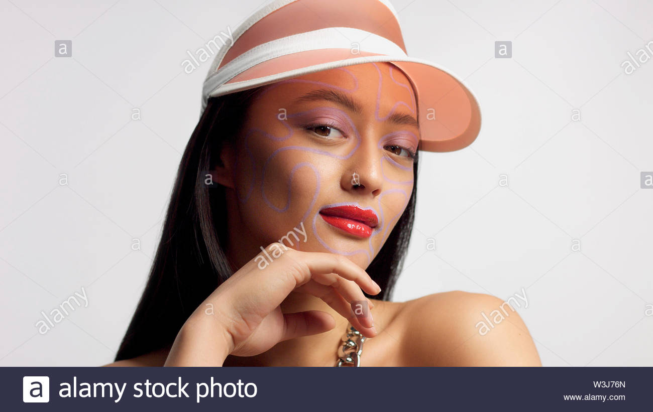 Mischlinge asiatische Modell im Studio kreative Kunst Make-up. Trägt ein Sun cap Beobachten an der Kamera. Helle Kreatives Make-up Stockbild
