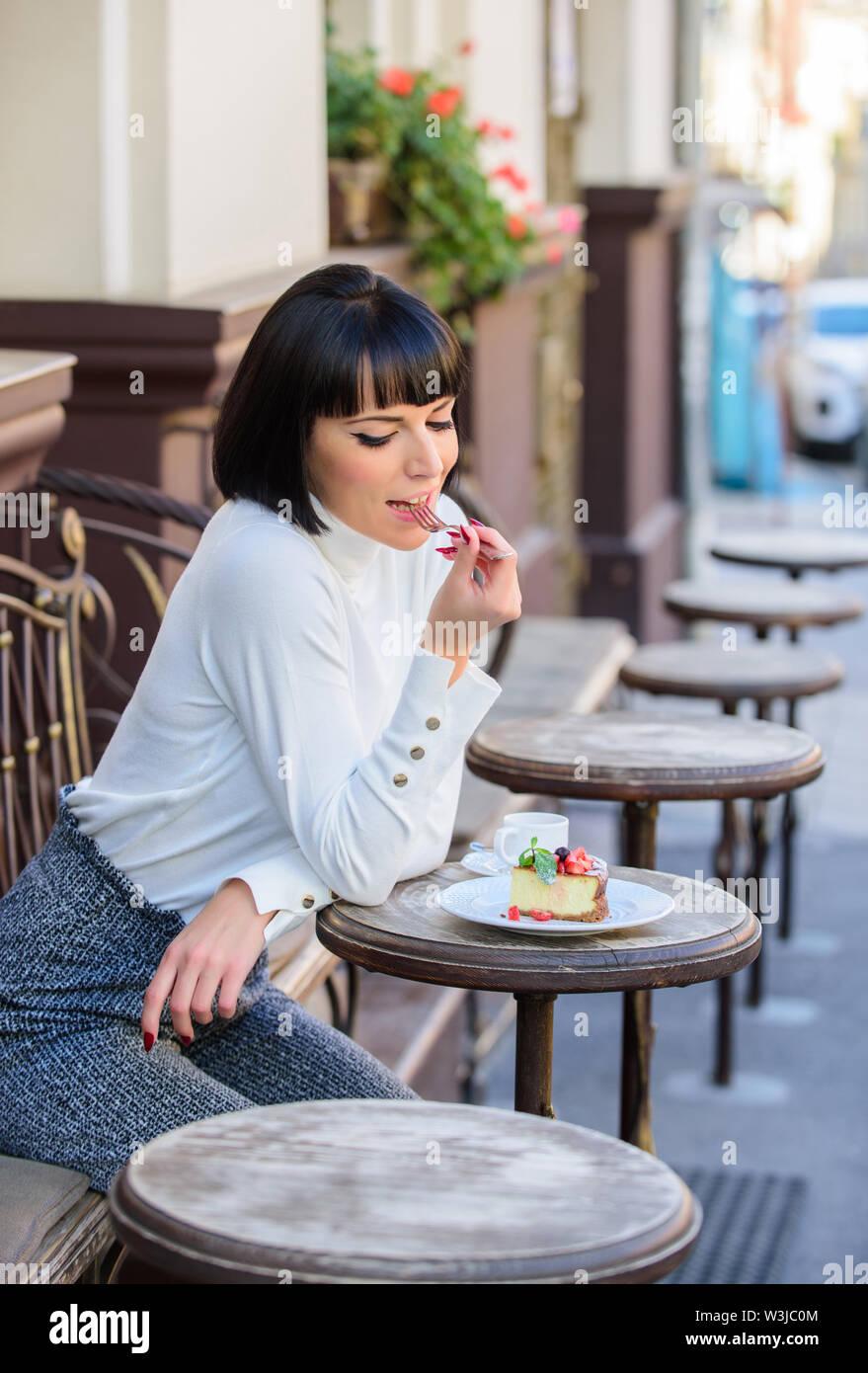 Hervorragender Geschmack. Frau attraktive Elegante brunette Essen gourmet Kuchen Cafe Terrasse Hintergrund. Angenehme Zeit und Entspannung. Köstliches Kuchen. Gir Stockbild