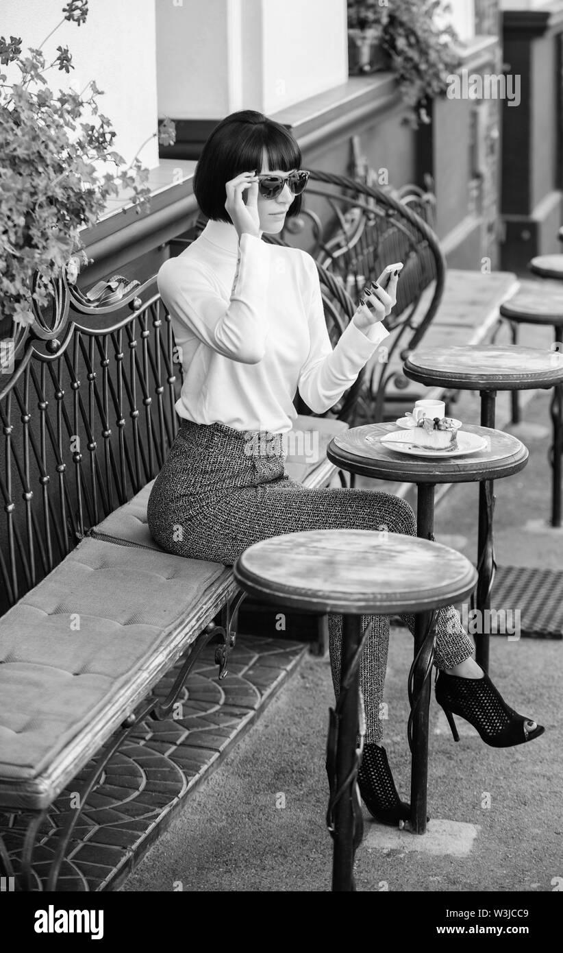 Freizeitaktivitäten Konzept. Mädchen Mode Dame mit Smartphone. Angenehme Zeit und Freizeit. Entspannen Sie sich und Kaffeepause. Frau attraktive Elegante brunette verbringen Lei Stockbild